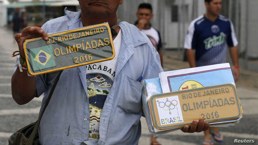 A street vendor offers unauthorized items for sale stamped with Olympic symbols and words along Copacabana beach in Rio de Janeiro, Brazil, July 28, 2016.