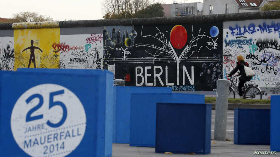 """A sign, which reads """"25 years Fall of the Wall 2014,"""" is pictured in front of sections at the East Side Gallery, the largest remaining part of the former Berlin Wall in Berlin, Nov. 3, 2014."""