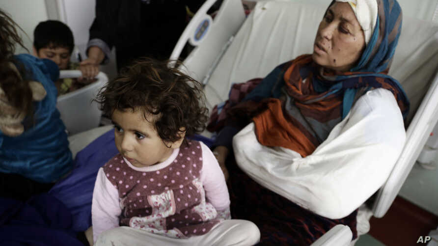 FILE - Um Yousef and her children recover in an Irbil hospital after they were badly injured in a mortar attack outside their home in Mosul, Iraq, Jan. 15, 2017.