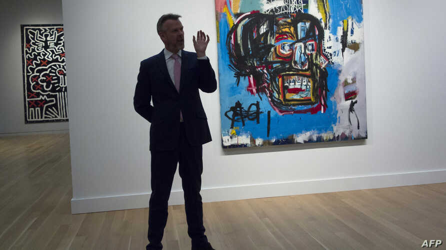"""A Sotheby's official speaks about """"Untitled,"""" a 1982 painting by Jean-Michel Basquiat during a media preview at Sotheby's in New York, May 5, 2017. The work sold for $110.5 million Thursday in New York, setting a new auction record for the US artist"""