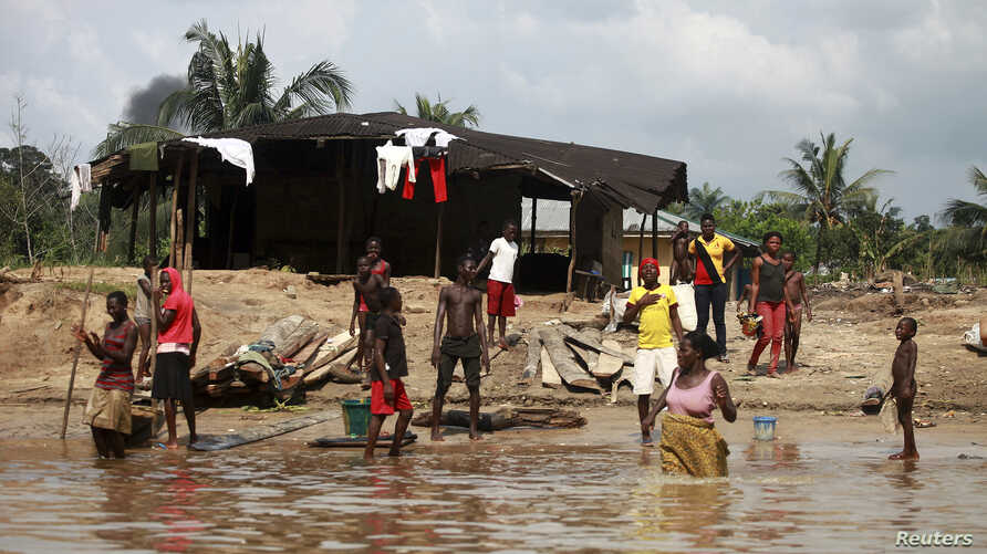 People wash and bathe in a village on the banks of the river Nun in Nigeria's oil state of Bayelsa, Nov. 27, 2012.