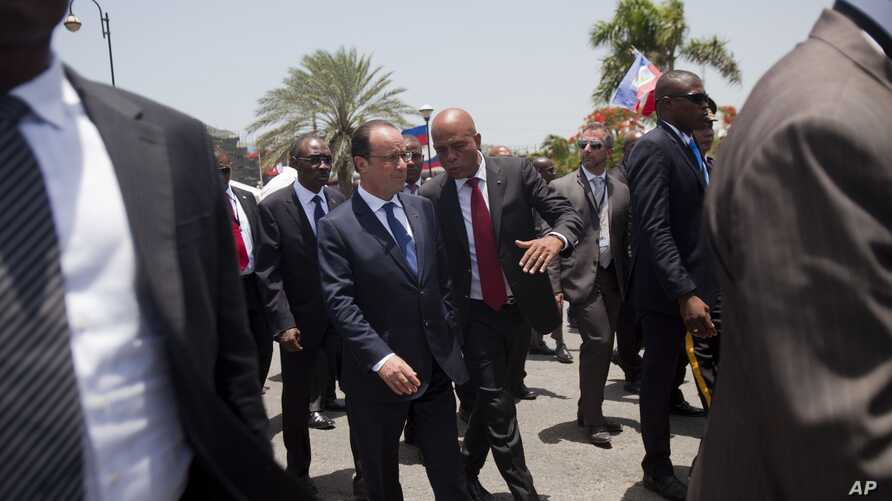 France's President Francois Hollande, center left, and Haiti's President Michel Martelly walk at the National Palace in Port-au-Prince, Haiti, Tuesday, May 12, 2015.