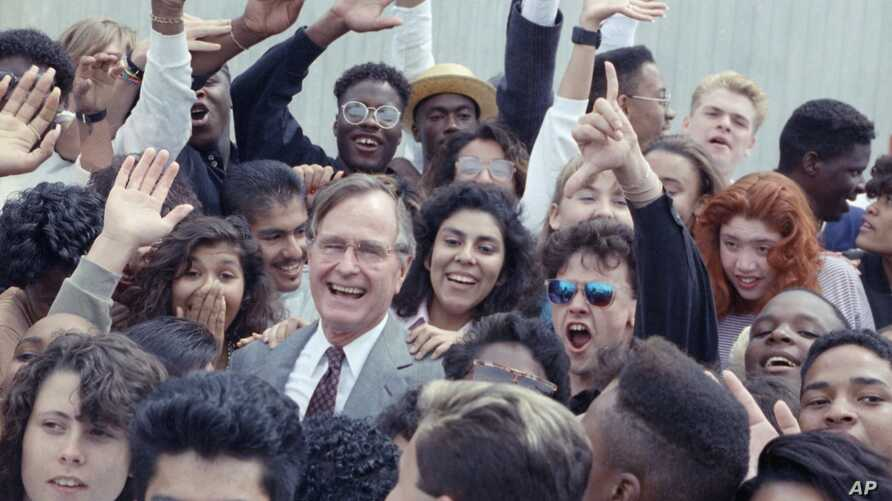 FILE - U.S. President George H.W. Bush is surrounded by cheering students from the Independent Living Program in Los Angeles, as Bush prepared to leave Los Angeles International Airport after presenting a Point of Light award in the area, May 21, 199