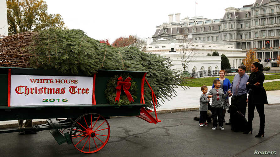 First lady Michelle Obama and her nephews, Aaron and Austin, welcome the White House Christmas tree  at the North Portico in Washington, U.S. Nov. 25, 2016. Tree farm owner Dave and Mary Vander Velden stand next to Mrs. Obama.