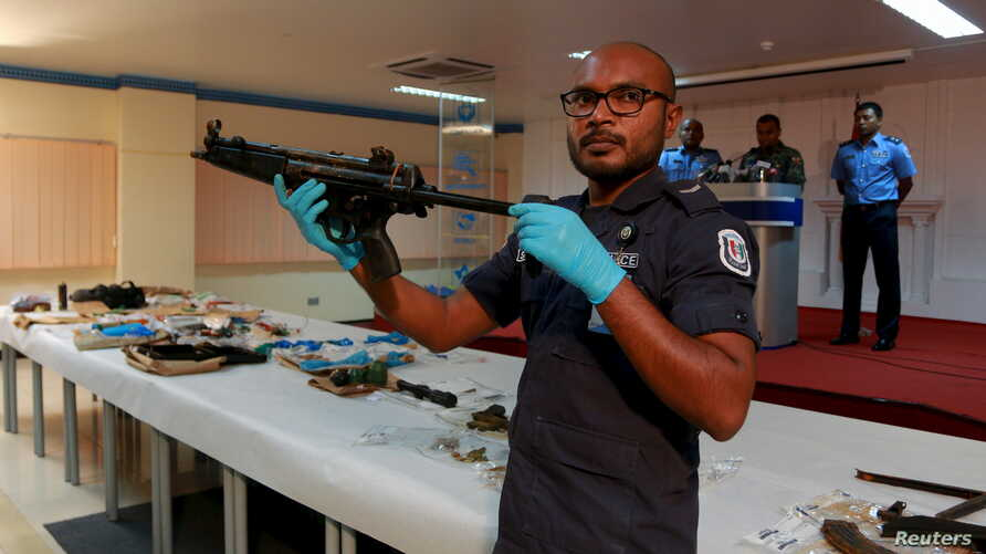 A Maldives police officer shows weapons found during investigations into a Sept. 28 blast on a speedboat transporting Maldives President Abdulla Yameen, October 31, 2015.
