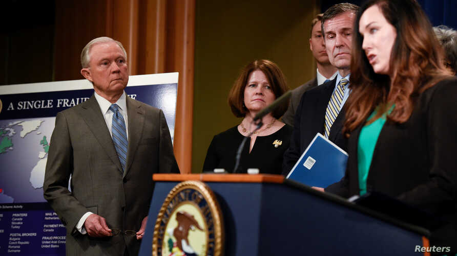 U.S. Attorney General Jeff Sessions listens to Angela Stancik (R) of Houston, Texas, speaking about her grandmother, a victim of fraud, during a news conference at the Department of Justice in Washington, Feb. 22, 2018.