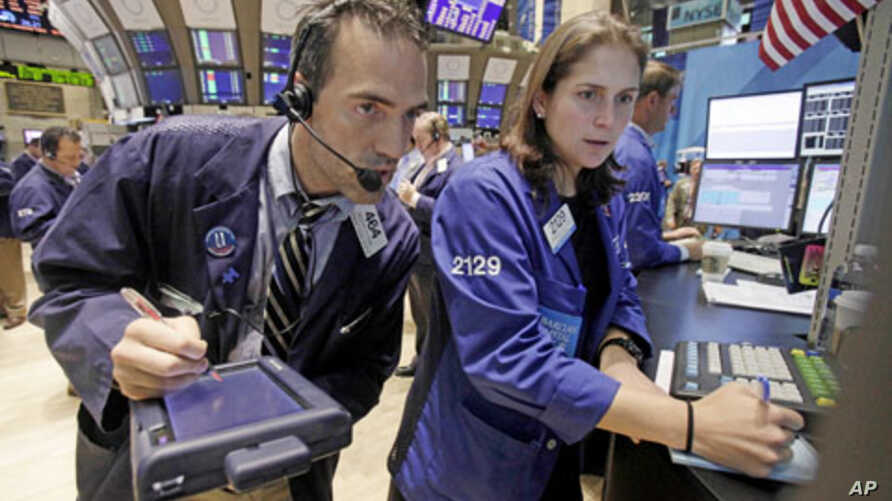Trader Gregory Rowe and specialist Jennifer Klesaris work on the floor of the New York Stock Exchange, Friday, Aug. 12, 2011