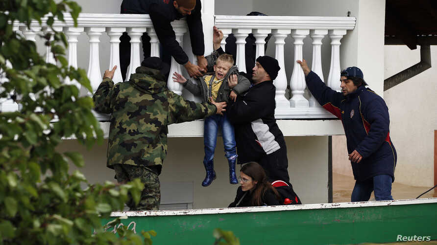 Serbian army soldiers evacuate a boy from a flooded house in the town of Obrenovac, southwest of Belgrade, Serbia, May 17, 2014.