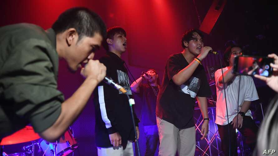 An audience member, second from right, raps with members of Rap Against Dictatorship on stage in Bangkok,  Oct. 27, 2018. The group has touched a nerve with an impassioned and now-viral music video lobbing fiery rhymes at the ruling junta.