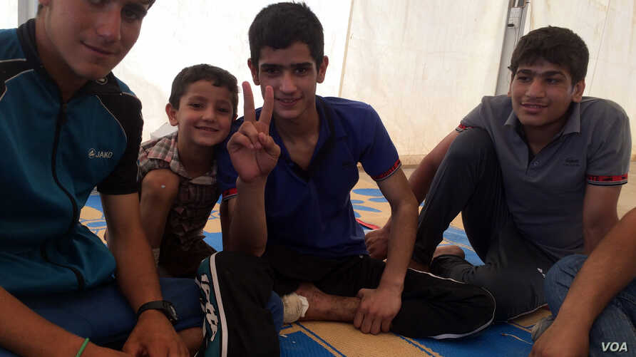 Mohammad, 16, (center) and his cousin and brother escaped IS militants three days ago after their house collapsed killing Mohammad's baby cousin and uncle. June 23, 2017 in Hammam Alil, Iraq. (H.Murdock/VOA)