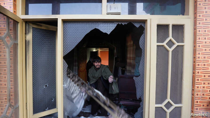 An Afghan man removes the burning items from the house of an Afghan member of parliament that was attacked by Taliban, Dec. 21, 2016, in Kabul, Afghanistan.