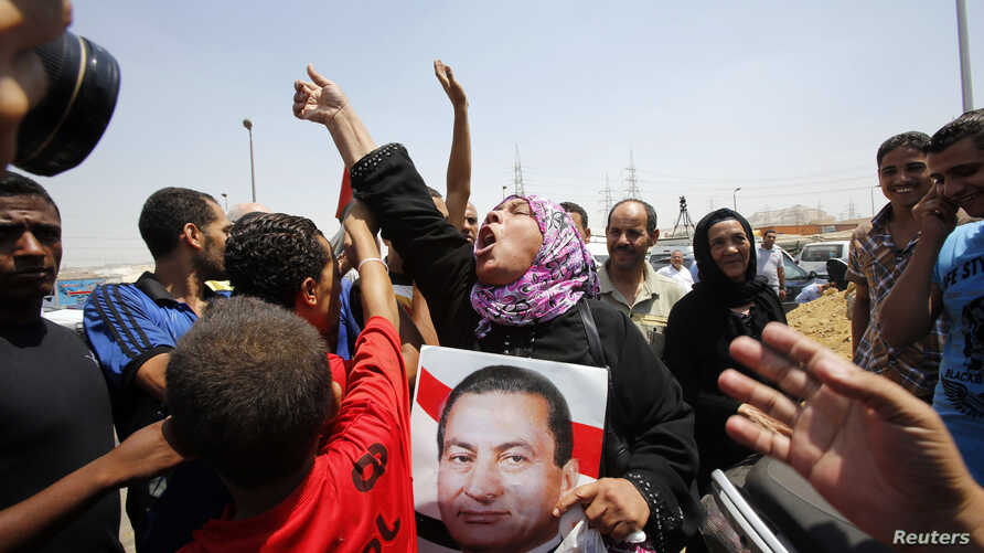 A supporter of former president Hosni Mubarak holds his poster to celebrate as she waits for his release in front of the main gate of Tora prison on the outskirts of Cairo, August 22, 2013.