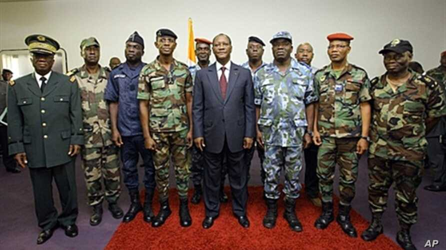 Ivory Coast's President Alassane Ouattara (C) poses with General Philippe Mangou (4L), chief of staff of former pro-Laurent Gbagbo Defense and Security Forces (FDS), and other military officers during a ceremony at the Hotel du Golf in Abidjan on Apr