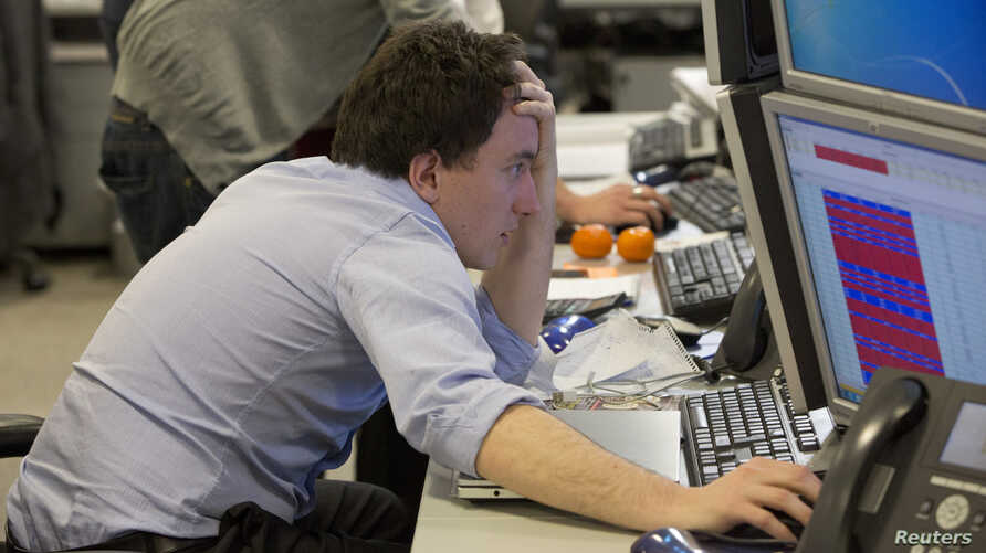 A trader looks at his screen on the IG Group trading floor in London March 18, 2013. The surprise decision by euro zone leaders to part-fund a bailout of Cyprus by taxing bank deposits sent shockwaves through financial markets on Monday, with shares