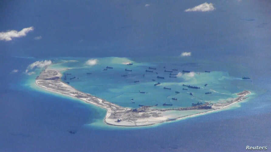 FILE - Chinese dredging vessels are purportedly seen in the waters around Mischief Reef in the disputed Spratly Islands in the South China Sea in this still image from video taken by a P-8A Poseidon surveillance aircraft provided by the U.S. Navy, Ma...