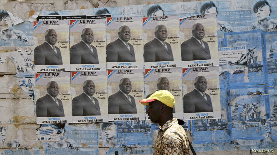 FILE - A man walks past election posters for opposition candidate Ayah Paul Abine of the People Action Party  in the capital Yaounde Oct. 7, 2011.