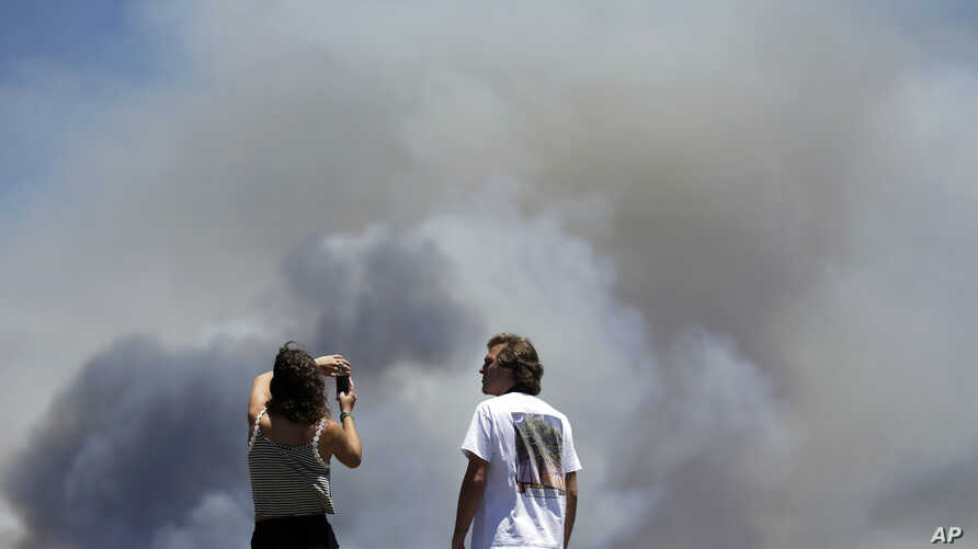 Chase and Brittany Boslet take pictures of smoke from the Las Pulgas fire burning on the Marine Corps Camp Pendleton near Oceanside, California, May 16, 2014.