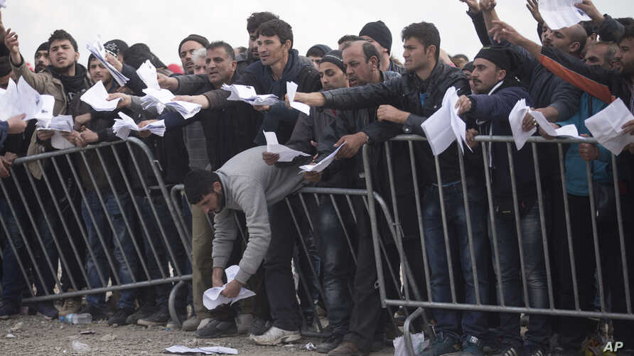Migrants wait behind bars to have errors in their transit documents corrected by Greek authorities at a camp in Idomeni, on the Greek-Macedonian border, March 3, 2016.