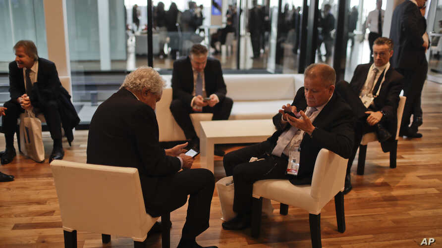 Businessmen check their phones during a break at Argentina's Business and Investment Forum in Buenos Aires, Argentina, Tuesday, Sept. 13, 2016.