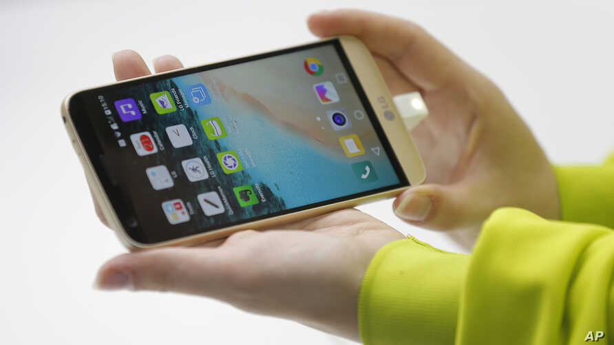 A woman shows the new LG's G5 smartphone during the LG unpacked 2016 event on the eve of this week's Mobile World Congress wireless show, in Barcelona, Spain, Feb. 21. 2016.
