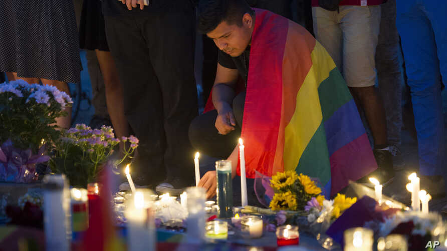 An unidentified man, wrapped in a Rainbow Flag, lights a candle during a vigil in Washington, Monday, June 13, 2016.