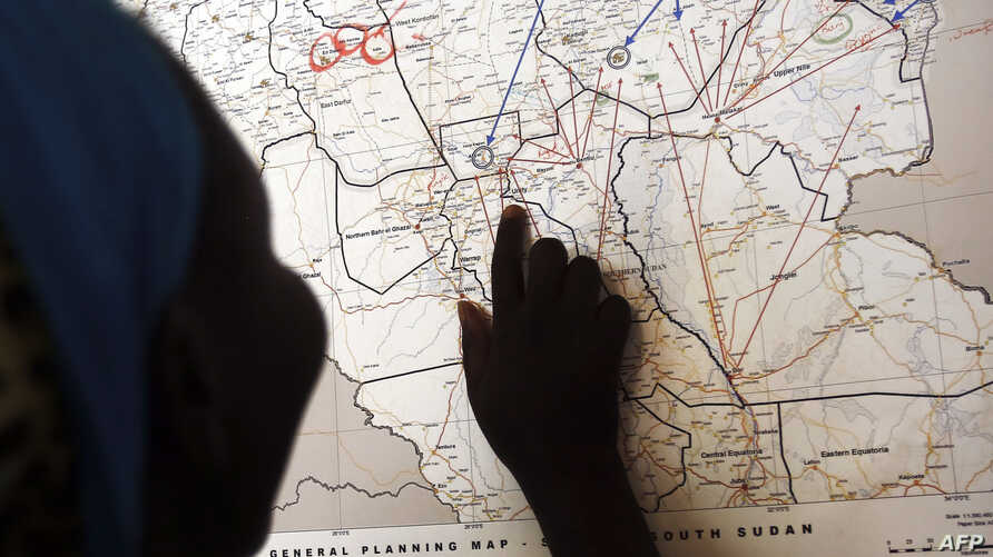 FILE - Evalina, a South Sudanese teenage victim of sexual abuse, points on a map to Unity state in South Sudan, indicating the location where she used to live, March 9, 2015. She said she escaped to Khartoum after being imprisoned by gunmen and sexua