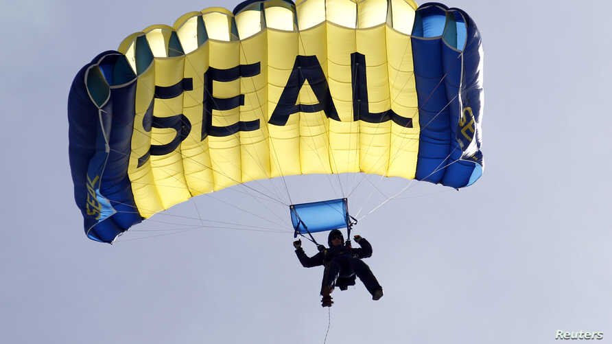 A U.S. Navy SEAL, who is a member of the Navy parachute team 'Leap Frogs', takes part in a demonstration of combat skills at the National Navy UDT-SEAL Museum in Fort Pierce, Florida November 11, 2011.