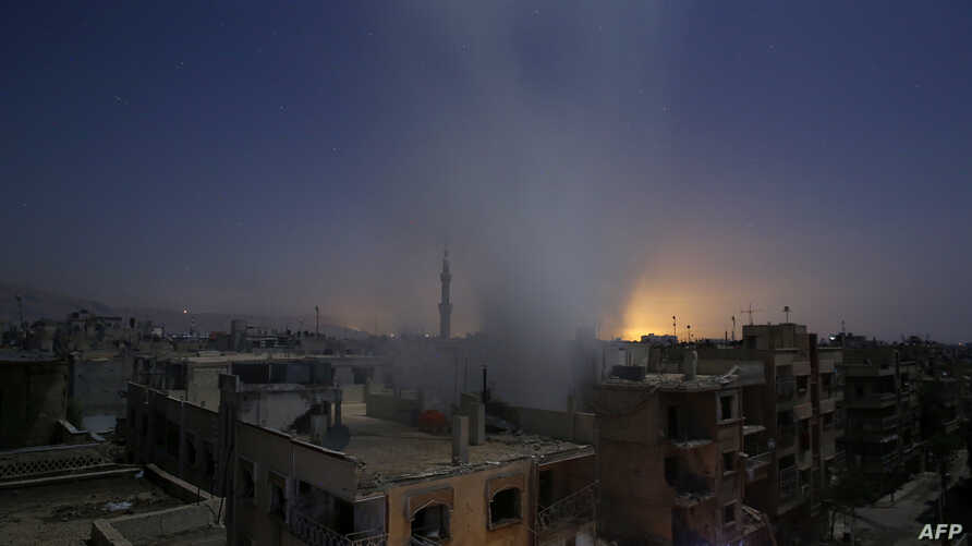 Smoke billows from a building early, Oct. 30, 2015, following reported shelling by Syrian government forces in the rebel-controlled area of Douma, east of Damascus.