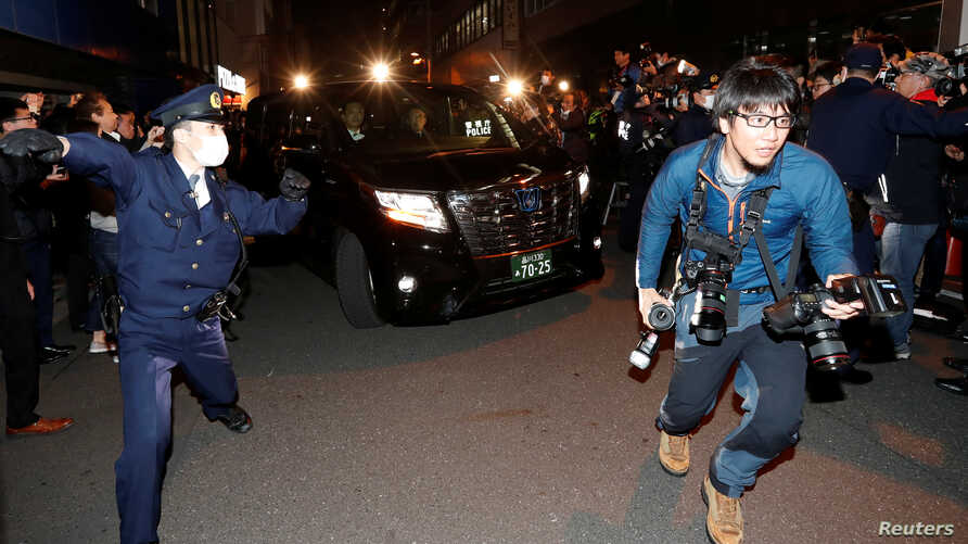 A car carrying former Nissan Motor Chairman Carlos Ghosn is surrounded by journalists as it leaves Ghosn's lawyer's office, in Tokyo, Japan, Mar. 6, 2019.