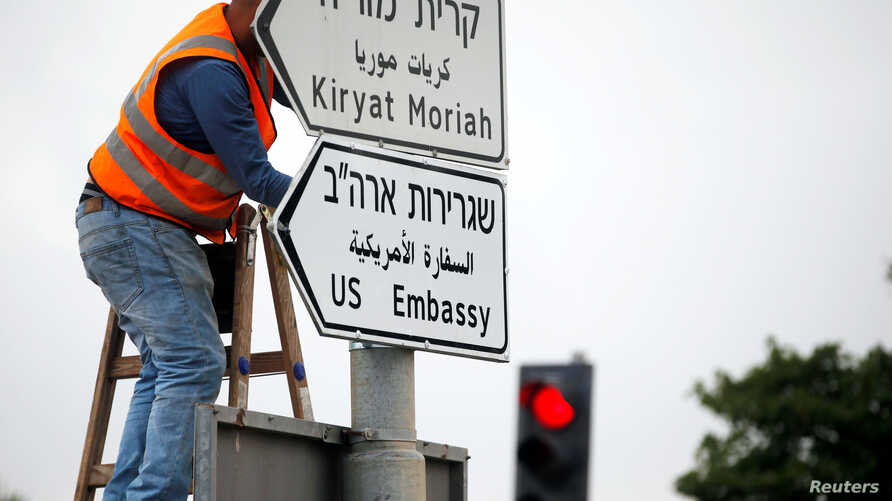 FILE - A worker hangs a road sign that directs traffic to the U.S. Embassy, in the area of the U.S. Consulate in Jerusalem, May 7, 2018.