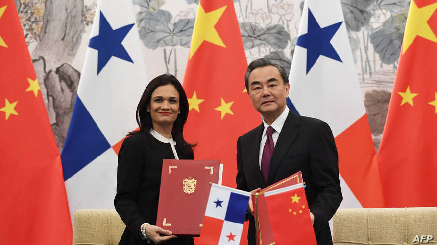Panama's Vice President and Foreign Minister Isabel de Saint Malo (L) and Chinese Foreign Minister Wang Yi pose with their documents after signing a joint communiqué on establishing diplomatic relations, in Beijing, June 13, 2017.