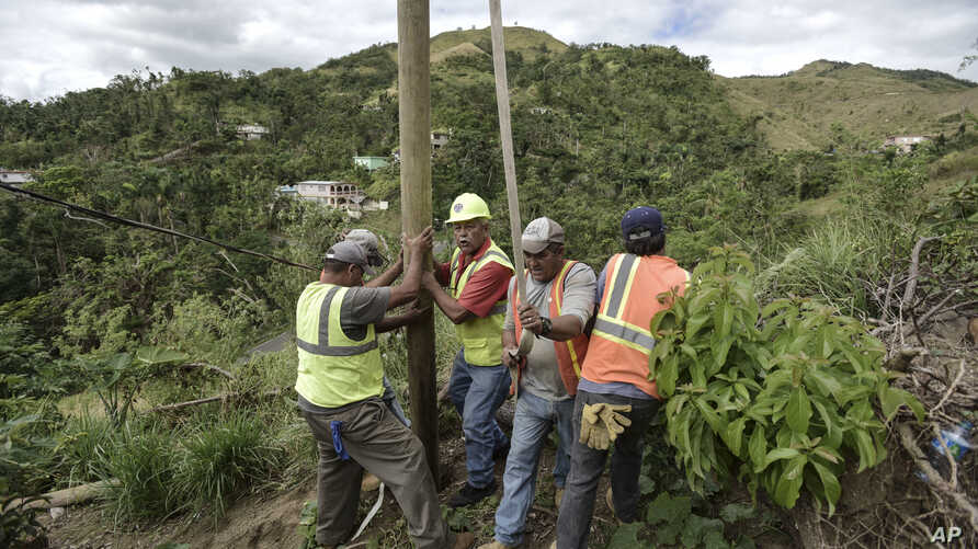 Public Works Sub-Director Ramon Mendez, wearing hard hat, directs locals who are municipal workers, Eliezer Nazario, holding rope, Tomas Martinez, right, and Angel Diaz, left, as they install a power pole in an effort to return electricity to Felipe