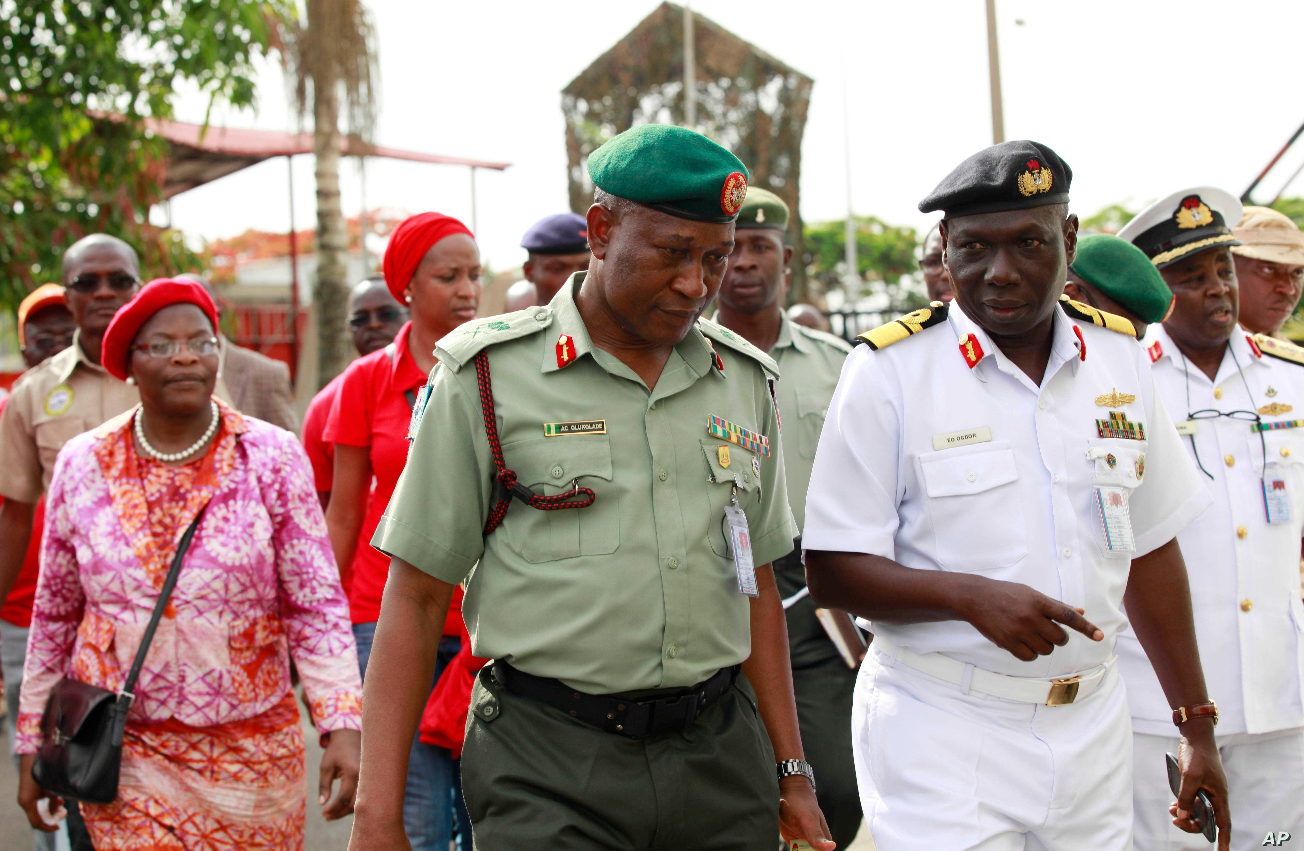 Brig. Gen. Chris Olukolade, Nigeria's top military spokesman, centre, walks with representatives of  kidnapped schoolgirls of Chibok secondary school, for a meeting at the defense  headquarters, in Abuja, Nigeria, May 6, 2014.