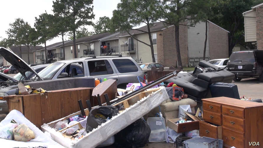 When the rains stopped in the Houston area for several hours Tuesday, residents pulled water-damaged carpets, furniture and other belongings out of their apartment buildings, leaving piles of debris outside their doors. (G. Flakus/VOA)