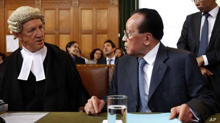 Cambodia's Deputy PM and Minister of Foreign Affairs Hor Namhong, right, and Franklin Berman, member of the English Bar, left, talk at the International Court of Justice in The Hague, Netherlands, May 30, 2011