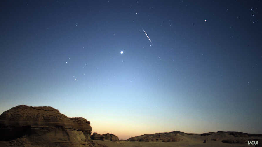 A meteor is seen in the sky during the Perseid Meteor Shower in the Valley of Whales, in Fayoum, Egypt, Aug. 12, 2017. (H. Elrasam/VOA)