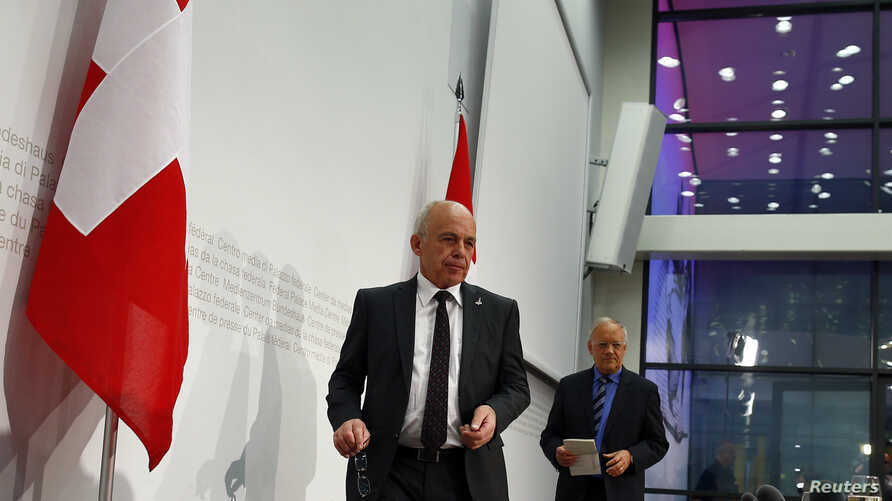 Swiss Defense Minister Ueli Maurer (L) and Economy Minister Johann Schneider-Ammann arrive for a news conference to discuss referendum results in Bern, Switzerland, May 18, 2014.