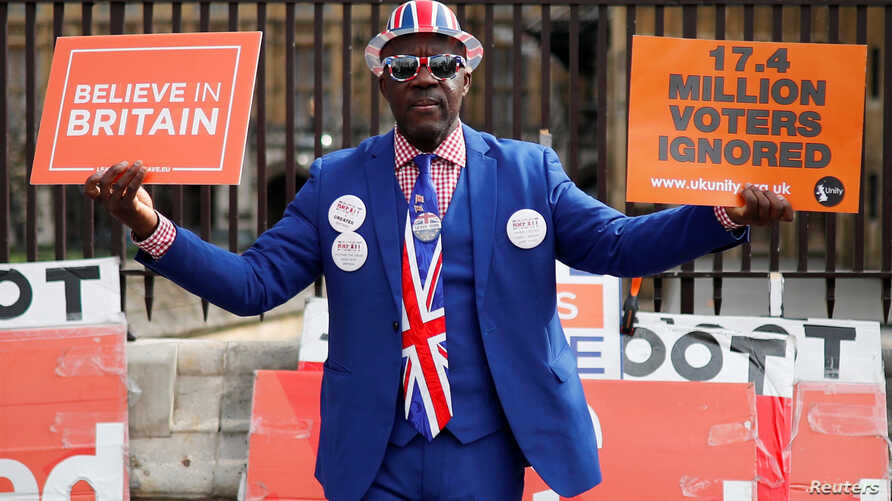 A pro-Brexit supporter holds placards outside the Houses of Parliament, following the Brexit votes the previous evening, in London, March 28, 2019.