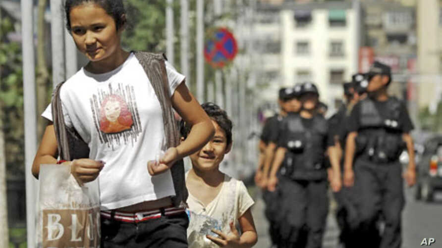 A woman and a child walk ahead of police officers patrolling on a street in Urumqi in northwest China's Xinjiang Uighur Autonomous Region, July 2, 2010. (file photo)