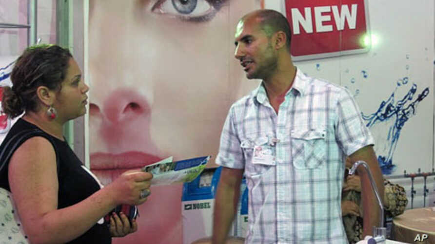 Wissem Abdennadher speaks to a potential customer at the Sfax business fair