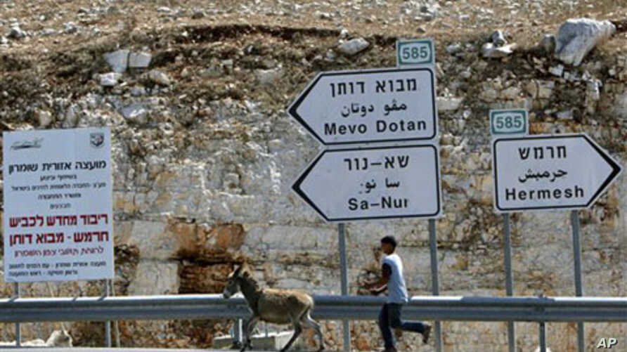 A Palestinian youth leads a donkey next to signs leading to Jewish settlements in the northern West Bank, 27 Sep 2010