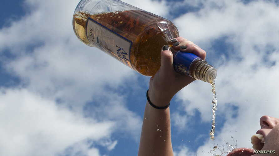 FILE - A woman pours alcohol from the bottle into her mouth, Oct. 17, 2015.