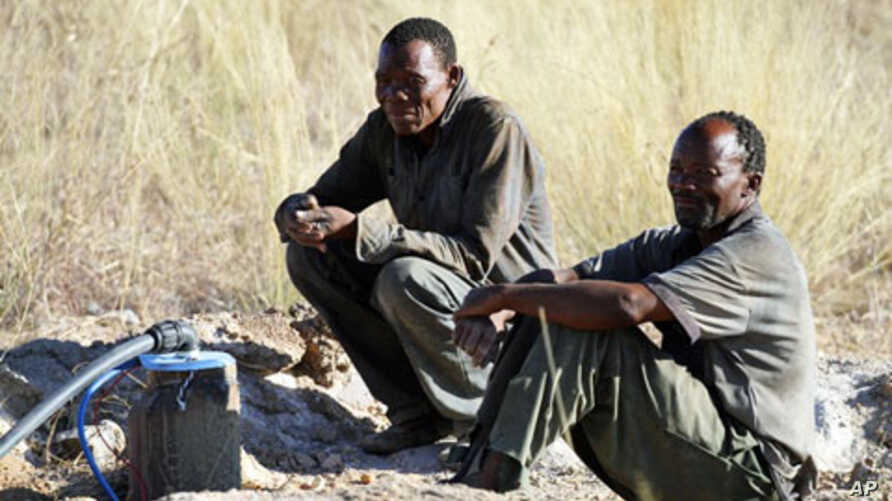 Two men from Kikao wait for water at the Mothomelo borehole