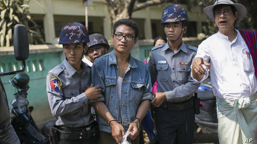 Police officers accompany Nyi Nyi Lwin, second from left, also known as Shin Gambira, a former Buddhist monk and a leader of the 2007- Saffron Revolution, to a courthouse in Mandalay, Myanmar, Feb. 16, 2016.
