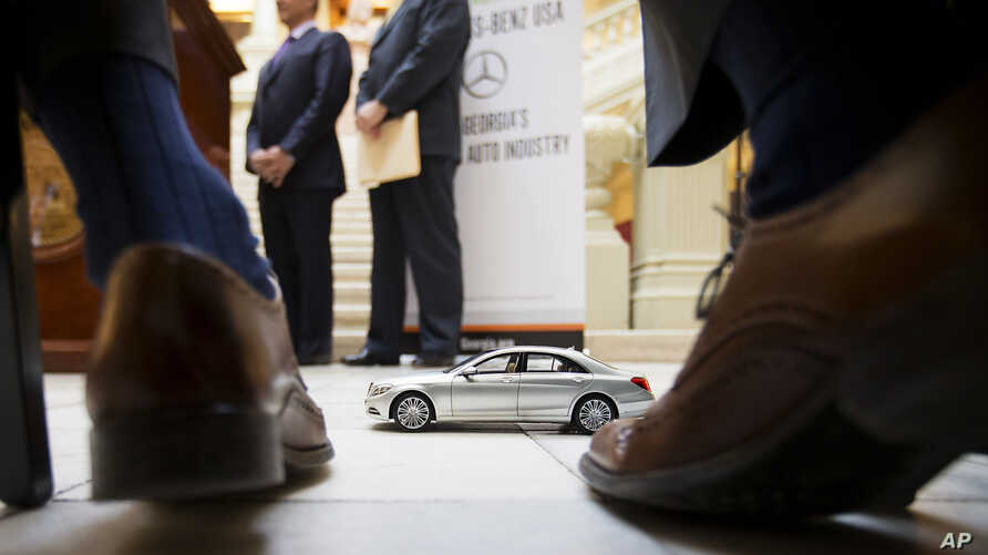 FILE- A model of a Mercedes-Benz sits in front of company officials as they wait to speak during a ceremony in Atlanta announcing the company's relocation of its U.S. corporate headquarters to Sandy Springs, Ga., from New Jersey, Feb. 3, 2015. German