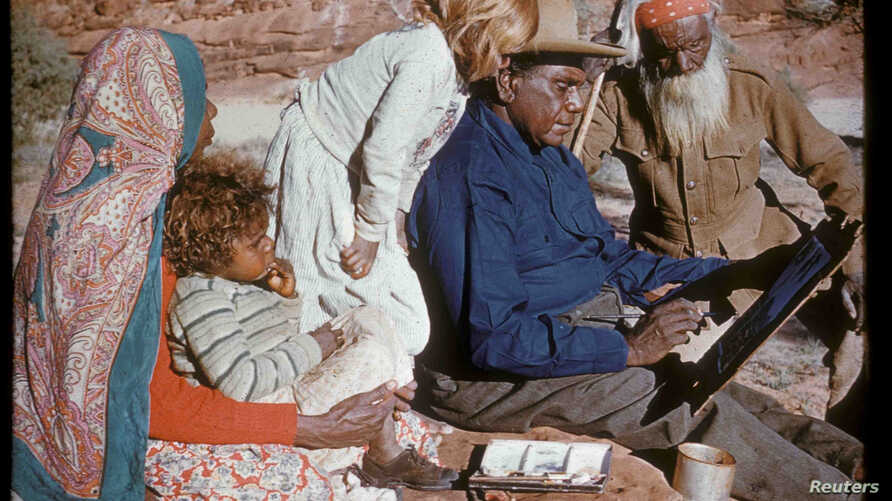 An undated photo released Oct. 14, 2017, shows family members watching Australia's most famous Aboriginal artist, Albert Namatjira, sitting on a rock as he paints.