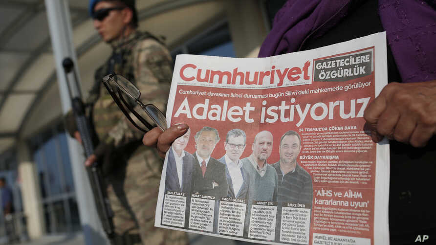 """Under the watchful eye of a Turkish army soldier standing guard outside a court, a protester holds a copy of the Cumhuriyet newspaper, with headline in Turkish reading: 'We want justice,"""" during a demonstration against the trial of journalists and st"""