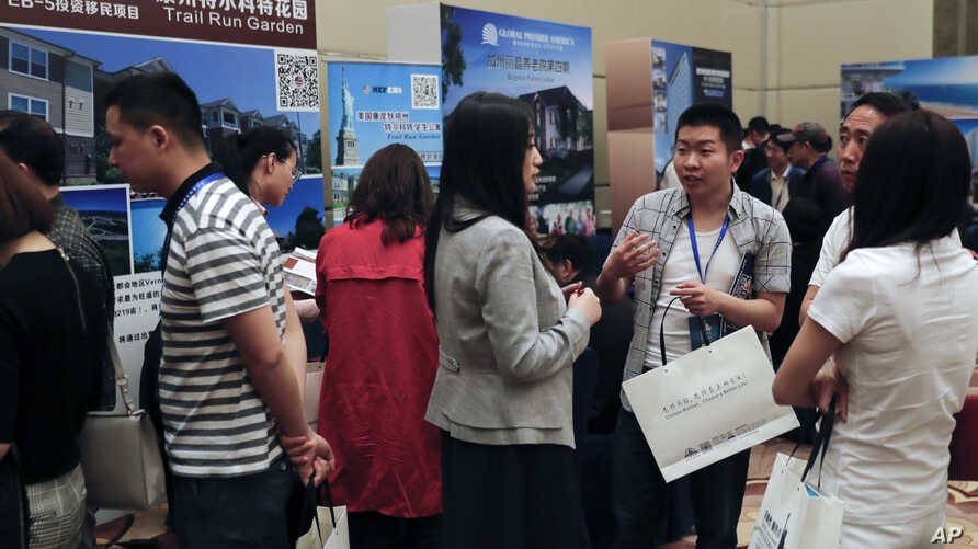 """Visitors chat as others seek information about the U.S. government's EB-5 visa program at the """"Invest in America Summit,"""" a day after an event promoting EB-5 investment in a Kushner Companies development was held, at a hotel in Beijing, May 7, 2017."""