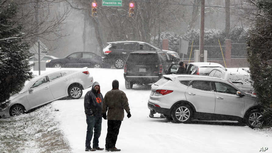 Motorists talk outside their cars after being involved in several accidents because of icy roads, Jan. 6, 2017, in Nashville, Tenn. Winter weather closed schools and made driving conditions hazardous.