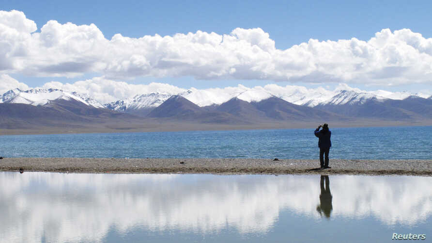 FILE - A tourist takes pictures at Namtso Lake in the Tibet Autonomous Region, Sept. 14, 2011.